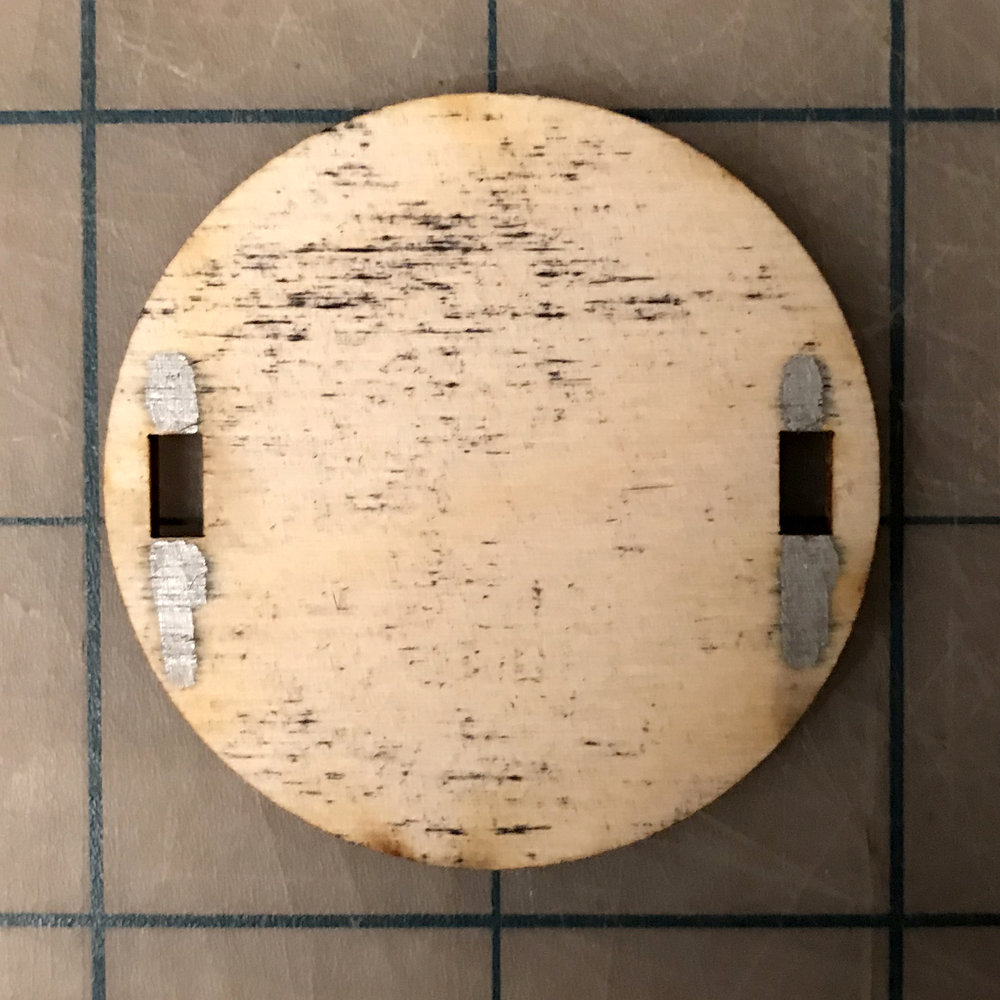 STEP TWO - PLACE CITY-PLATE FACE DOWN ON A FLAT SURFACE. NOTE THE PLATE ORIENTATION. WHILE THIS IS A PRESSURE FIT DISPLAY RACK, A TINY DAB OF GLUE IN THE SILVER AREAS SHOWN WILL ADD STRENGTH.