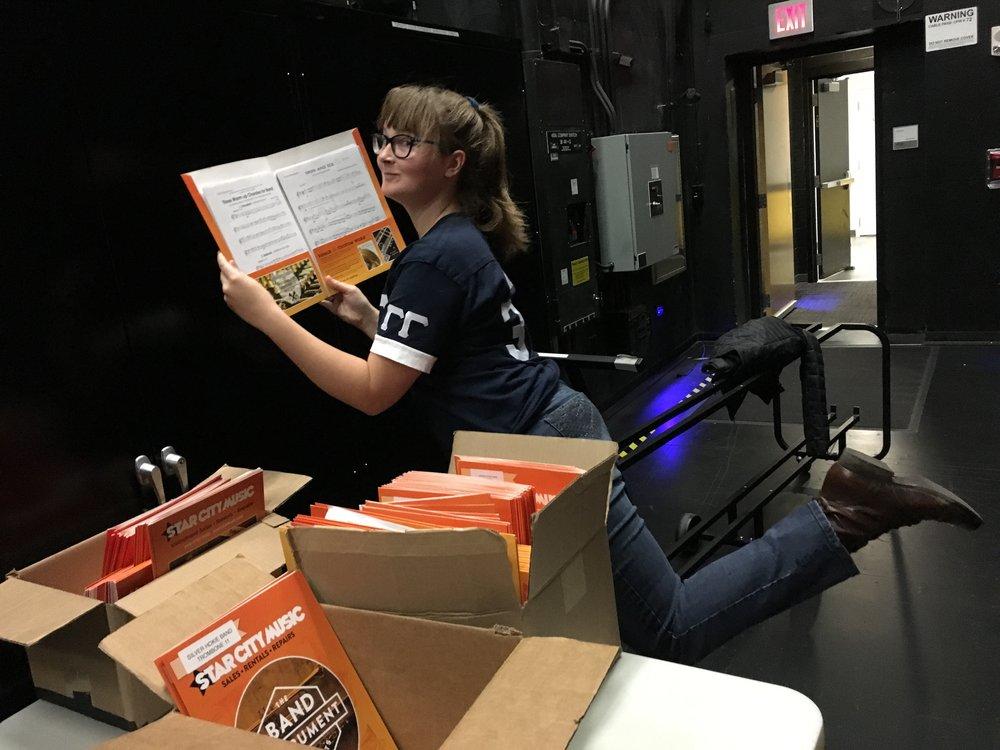 Sara Elwood, Alumni Secretary of Tau Beta Sigma, holding a music folder; Source; Alana Hassett