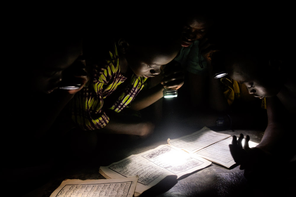 Children read the Koran by flashlight at a mosque in Wantugu, Northern Region, Ghana on May 13, 2007. Wantugu had power lines installed in 2000, but government officials failed to connect them to a power source.