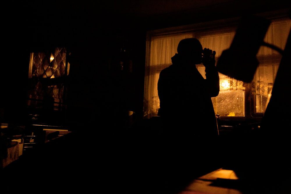 """Richard Latham has a late-night drink in his home in Solihull, England, February 19, 2012. When Richard and his wife separated four years ago, he was left with a £400 energy bill that he is unable to pay off. He has not used heat in his home since then, and very rarely turns on light or electrical appliances, for fear of increasing his debt. """"I'm a bit paranoid about power,"""" he says."""