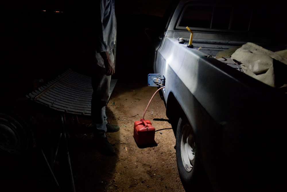 A man siphons gasoline out of his truck so that he can use it to power a generator for a couple of hours in his trailer in Pajarito Mesa, New Mexico, USA on May 28, 2010.