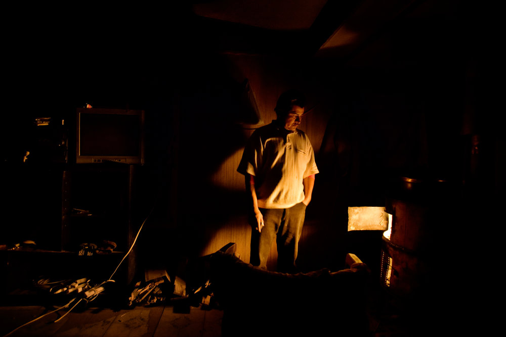 Epifanio Alcudia stands by the heat of a wood stove in his trailer in Pajarito Mesa, New Mexico, USA on Feb. 8, 2011.