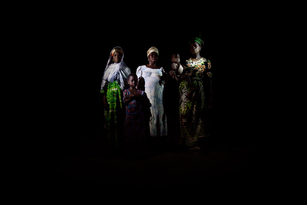 The women and children of the Abubakari household pose for a portrait lit with flashlights in Voggu, Northern Region, Ghana on Feb. 20, 2010. Women bear the heaviest burden of living without electricity, as they walk for miles to fetch firewood and bring grains to nearby villages to be processed by electronic machinery.