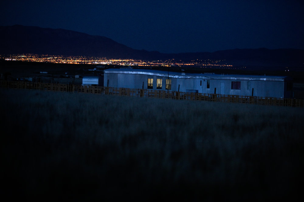 The lights of nearby Albuquerque shine in the distance behind a trailer in Pajarito Mesa, New Mexico on May 24, 2010.
