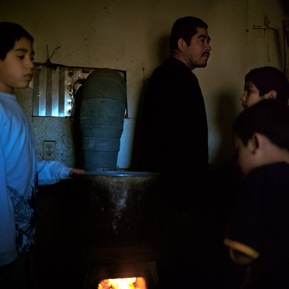 Members of the Alcudia family crowd around a wood stove for warmth in the early morning in Pajarito Mesa, New Mexico, USA on Feb. 12, 2011.
