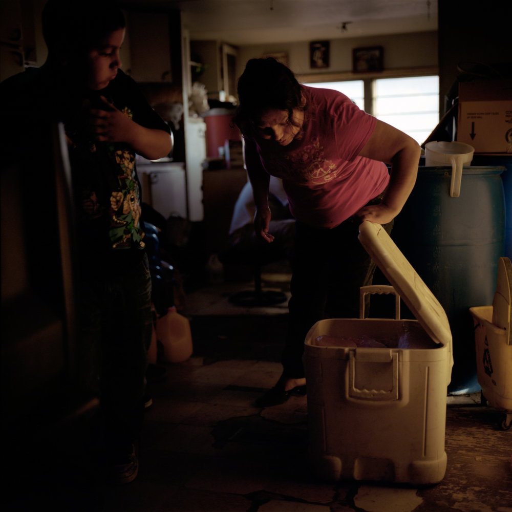 Esperanza Sanchez and her son, Ricardo Alcudia, peer into a cooler that they use for food storage at their home in Pajarito Mesa, New Mexico, USA on Feb. 18, 2011. The family owned a refrigerator, but sold it because they needed the money and wanted to reduce their household energy expenses.
