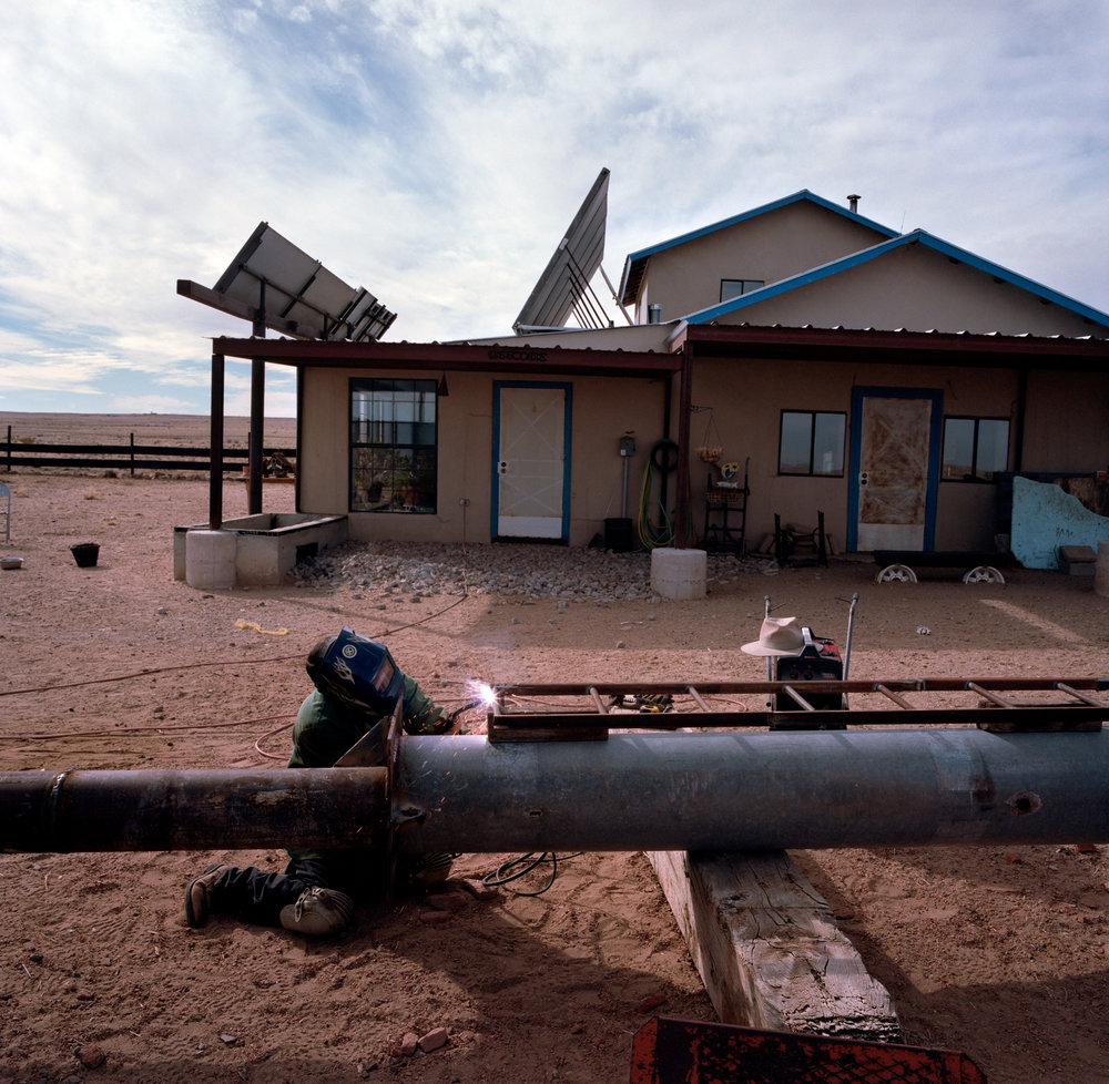 Carlos Proffit uses a solar-powered welder to build a home-made wind turbine from scraps of metal at his home in Pajarito Mesa, New Mexico, USA on Feb. 15, 2011.