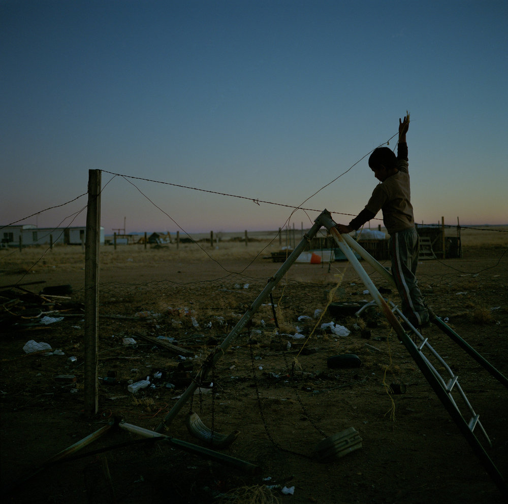 A child plays outside of his home in Pajarito Mesa, New Mexico, USA on Feb. 12, 2011.