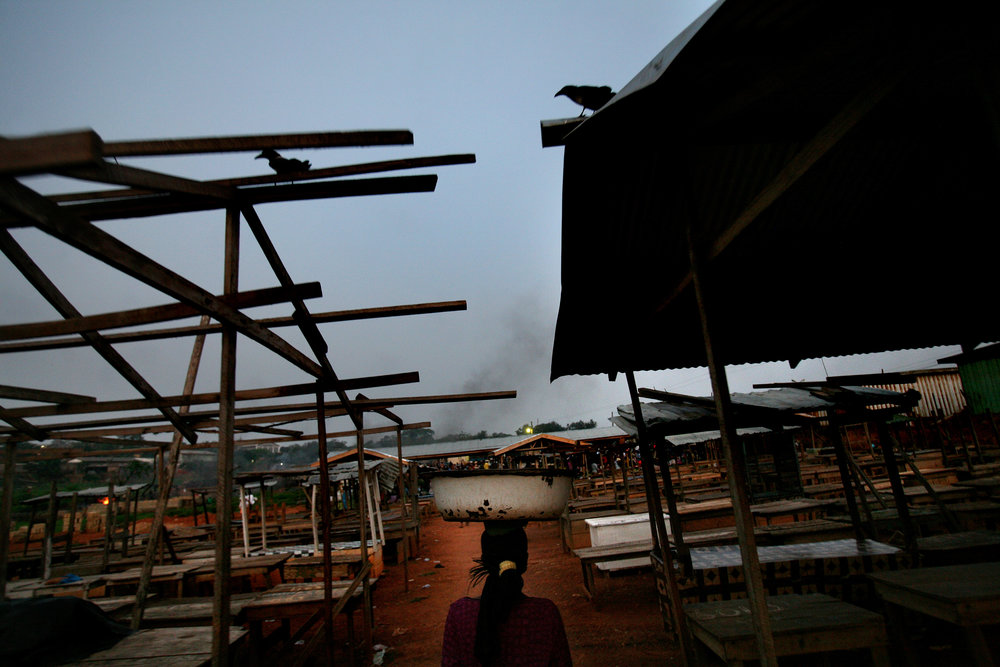 Alietu, a Kayayo girl, walks to Racecourse Market in Kumasi, Ghana to start her workday on Feb. 23, 2009.