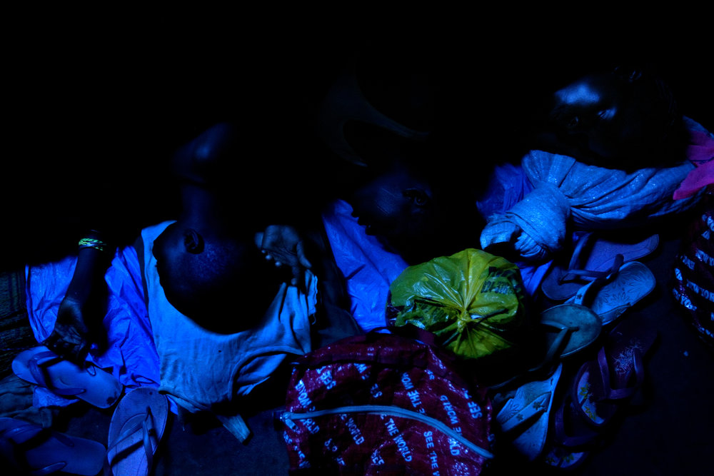 Kayayo girls huddle together while sleeping on the floor of a former warehouse where several hundred of them live in Kumasi, Ghana on Feb. 26, 2009.