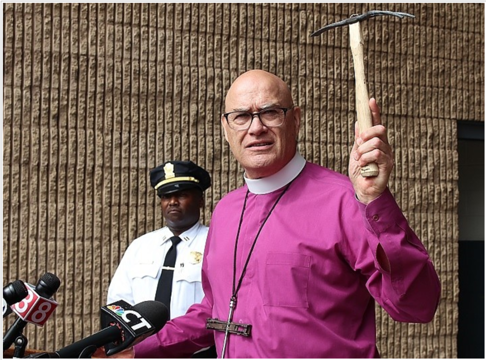 Retired Bishop Jim Curry with the two-sided mattock made of old gun parts at Thursday morning's presser.