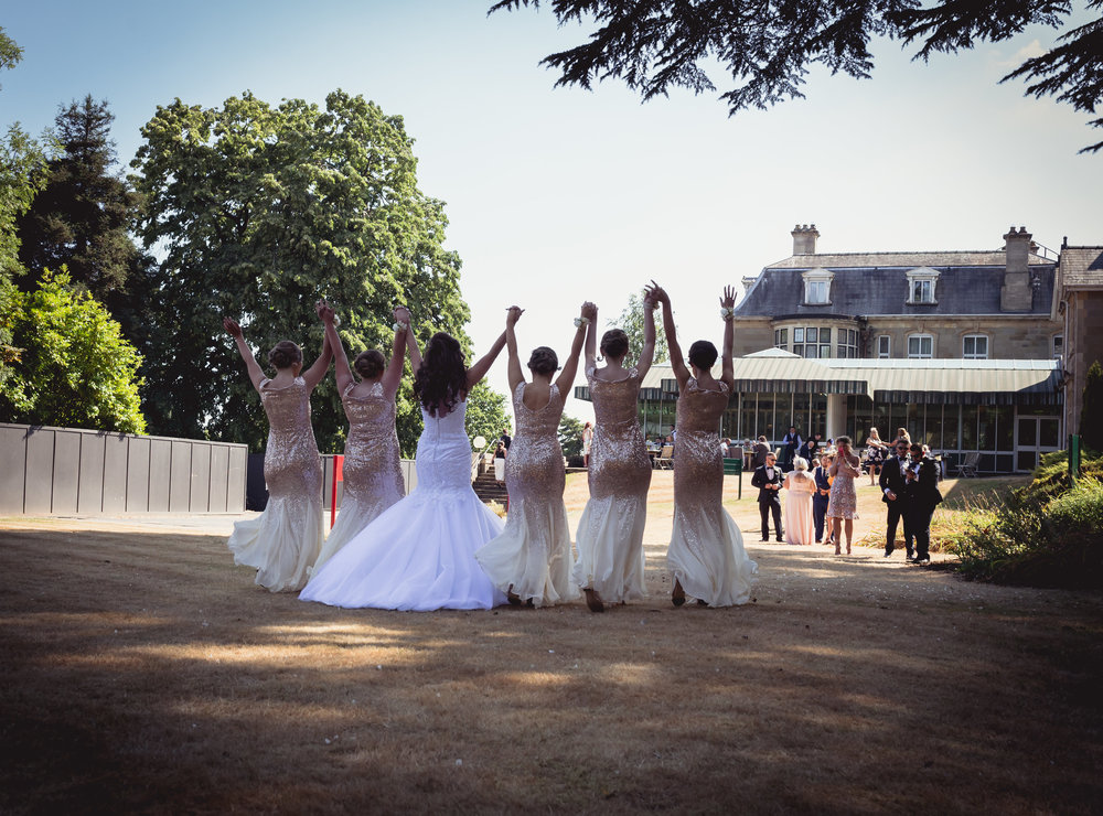Bride and bridesmaids walking with hands in the air at Celtic Manor Resort in South Wales