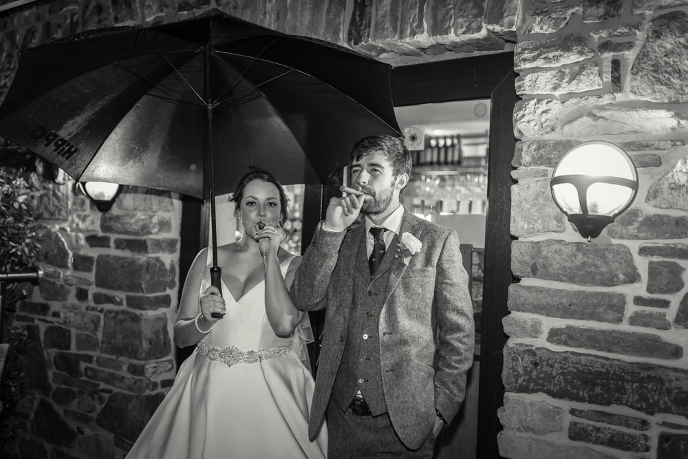 Bride and Groom enjoying a cigar after their wedding at Canada Lodge near Cardiff