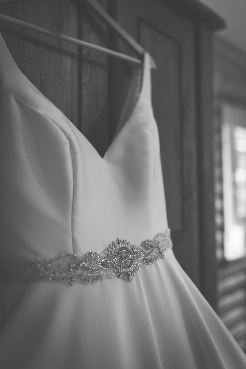 A close up black and white photograph of a wedding dress