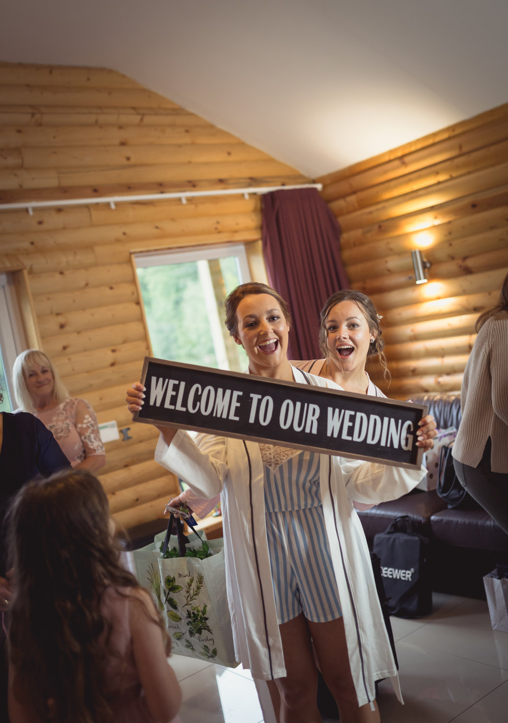 Bride and her sister holding a welcome to my wedding sign