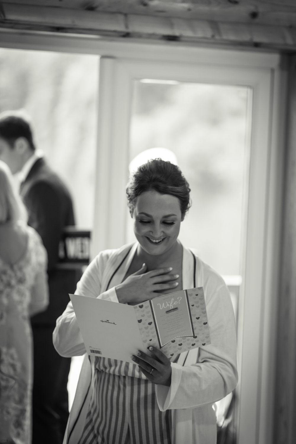 blak and white photograph of an emotional bride reading her congratulations cards