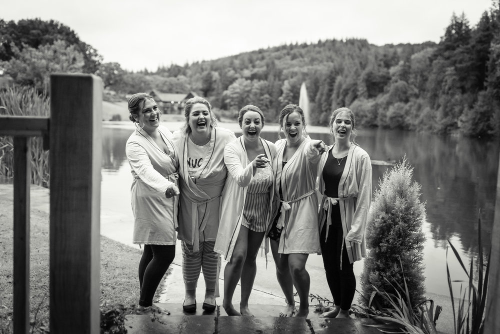 A black and white photograph of a bride and her bridesmaids laughing
