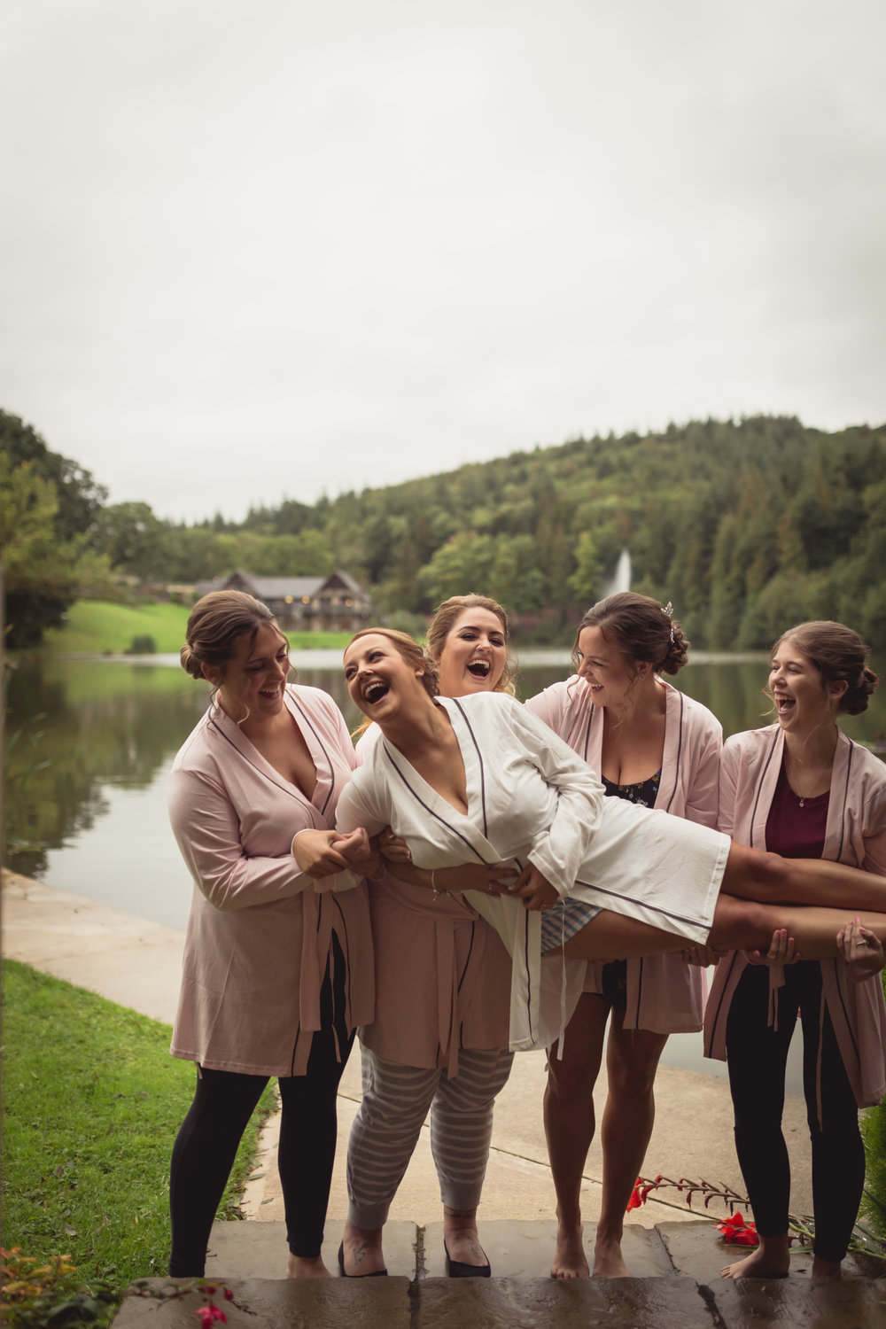 Bridesmaids carrying bride and laughing out loud next to a lake