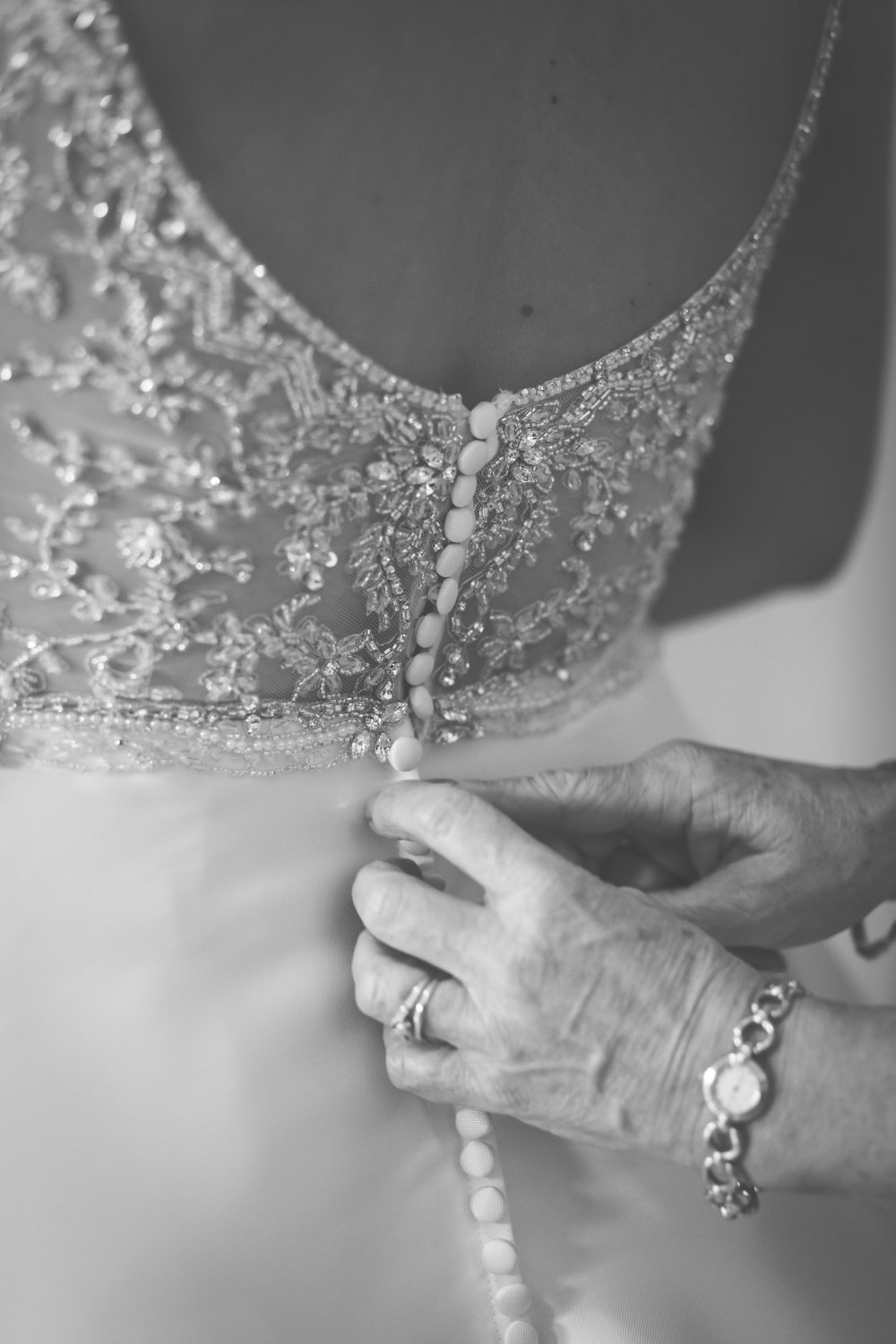 Mother of bride doing up buttons on the wedding dress