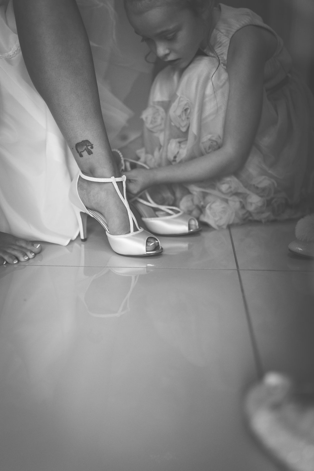 Black and white image of a flower girl doing up the strap on the brides wedding shoes