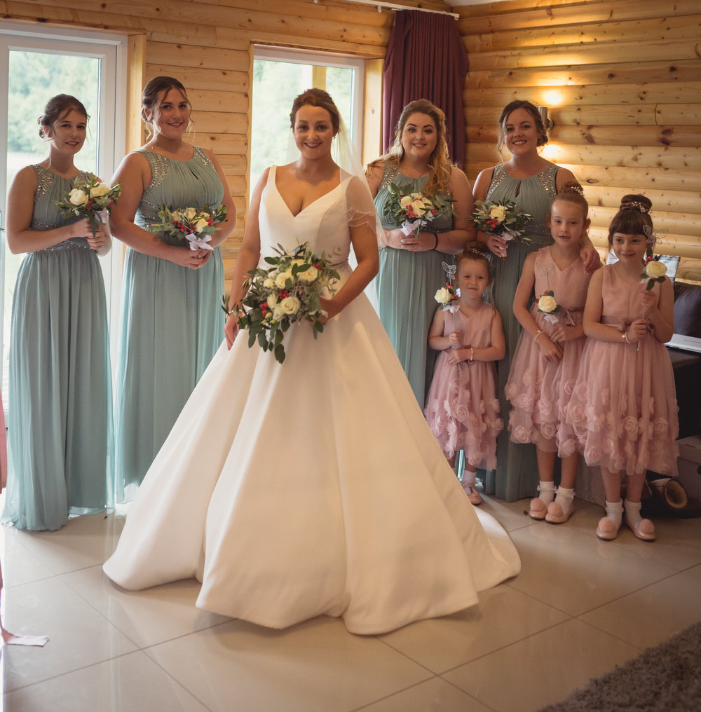 A group photograph of the bride along with her four bridesmaids and her two flower girls
