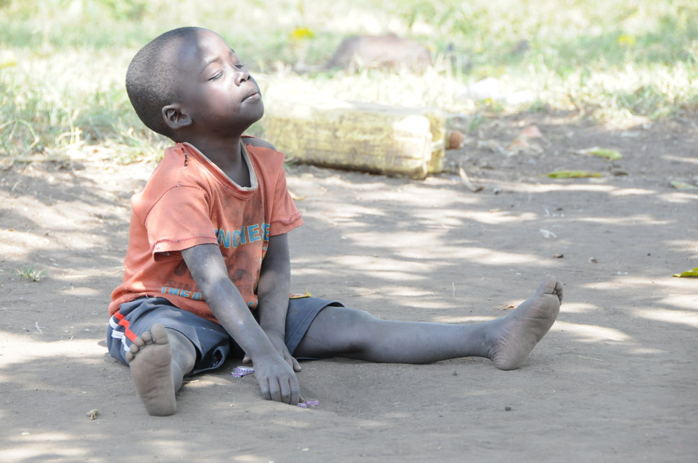Augustine's vision is poor due to bilateral cataracts. This makes it difficult for him to play with other children. Here he is playing with bottle tops in the dusty compound of his home.