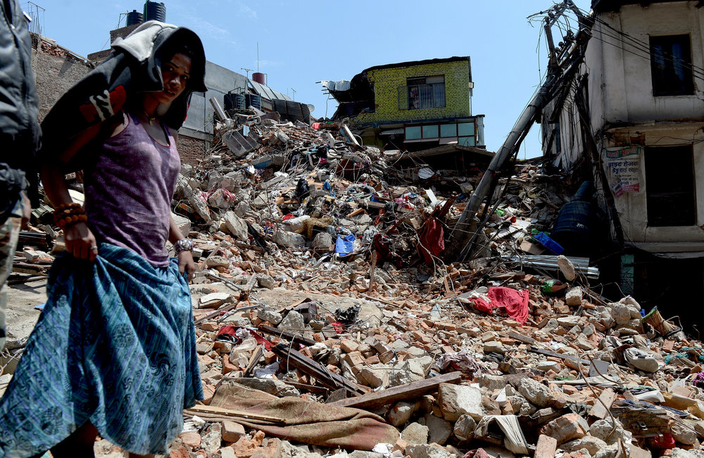 A woman is standing next to the rubble of a house.
