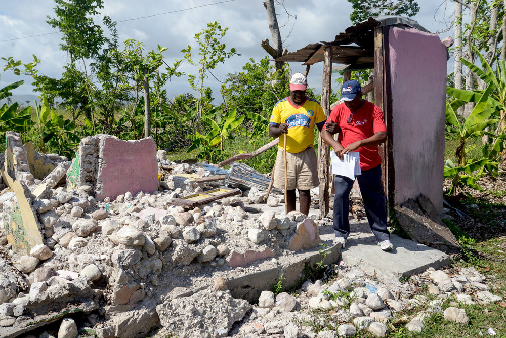A CBM staff member helps a man walk through the rubble with his cane