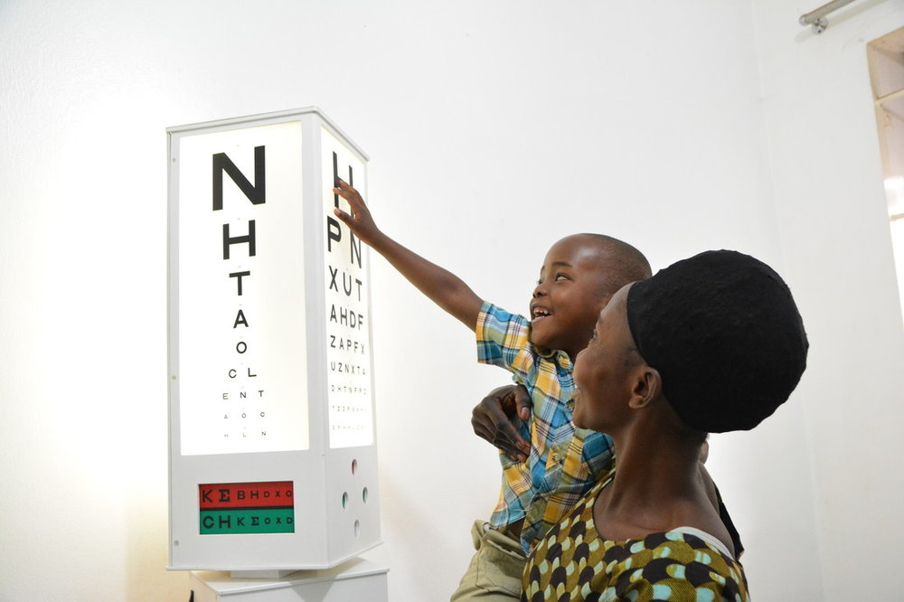 Shakulu, in his mother's arms, looks at the eye test chart.