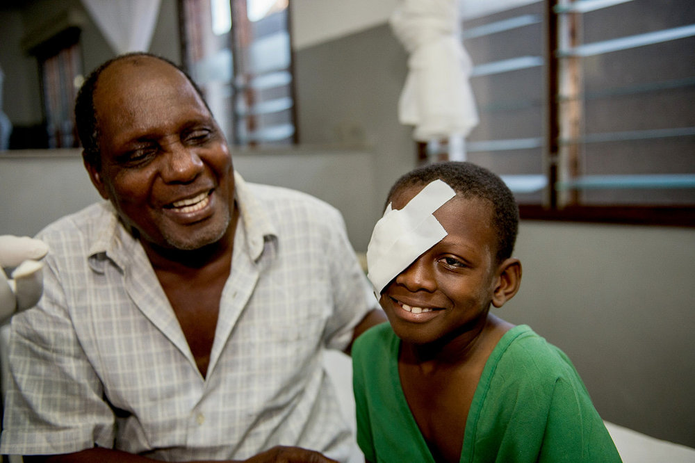 Omari and his father, Amiri can't stop smiling as a doctor comes and removes the bandages after Omari's cataract surgery.