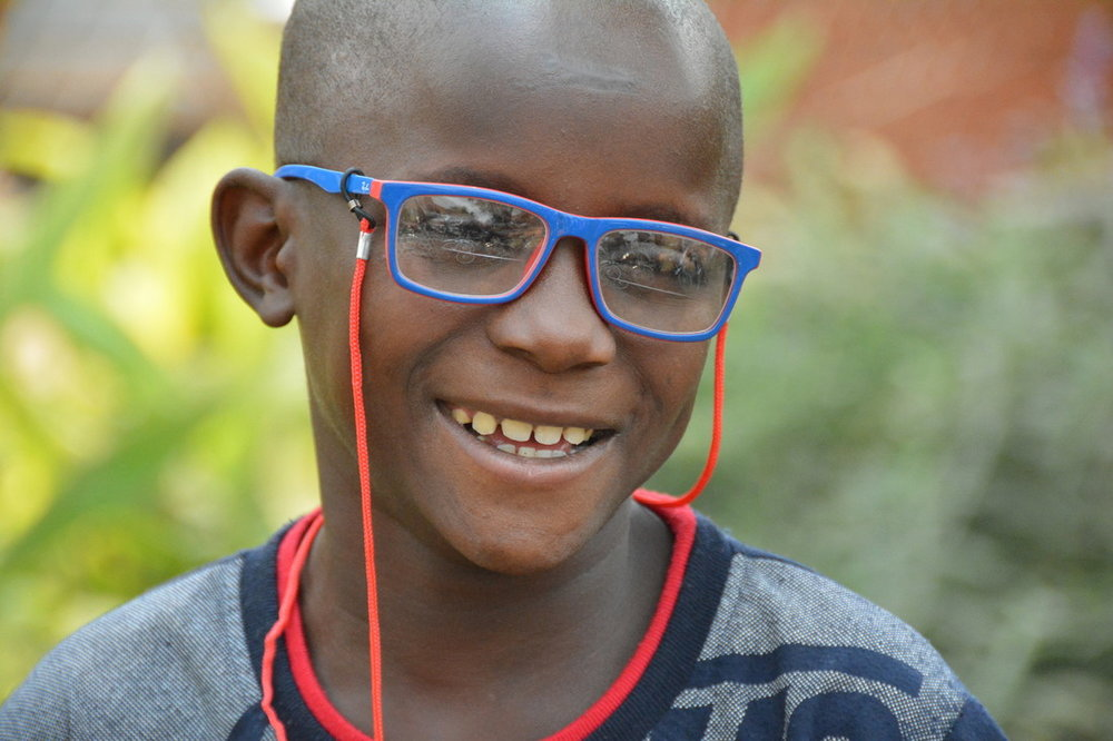 Mathias from Uganda with his new glasses after his sight-saving cataract operation