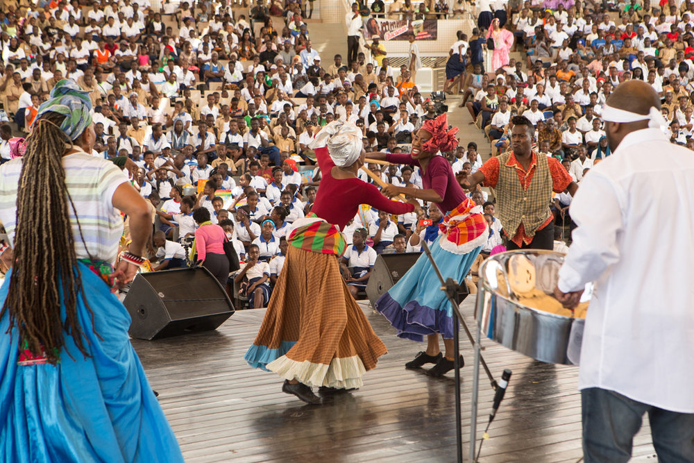 "A ""stickfight"" scene from Brooklyn based Trinidadian carnival band Jouvayfest performance for an audience of thousands of schoolchildren at the Palais de la Culture, Abidjan. JouvayFest also opened the festival with a parade through the lively streets of Treichville to the Palais de la Culture. The paraders made up of rhythm section, steel pan, members of Pagwah Jouvert band and Something Positive dance company."