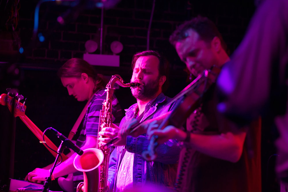 Stuart Bogie on sax, center Brian Webre, sampler, left, and Louis Michot violin