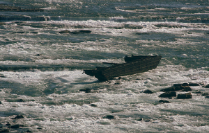 The scow, firmly wedged in between the rocks of the river.
