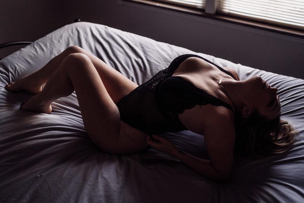 Boudoir Portrait woman in black bodysuit laying on bed
