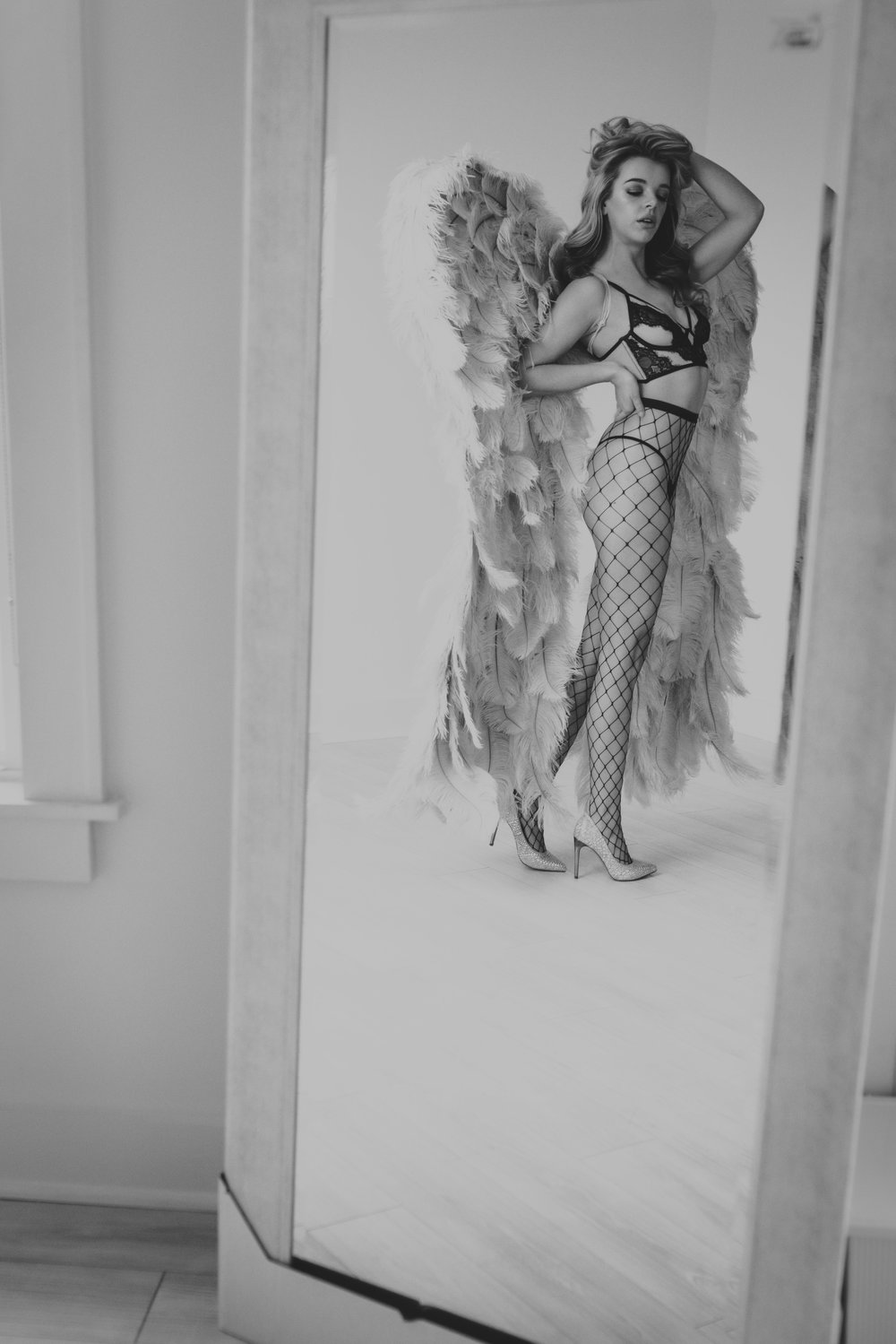 Oklahoma City Boudoir session woman wearing angel wings looking in mirror