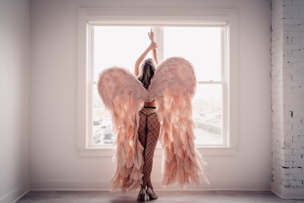 Oklahoma City Boudoir session woman wearing angel wings looking out the window