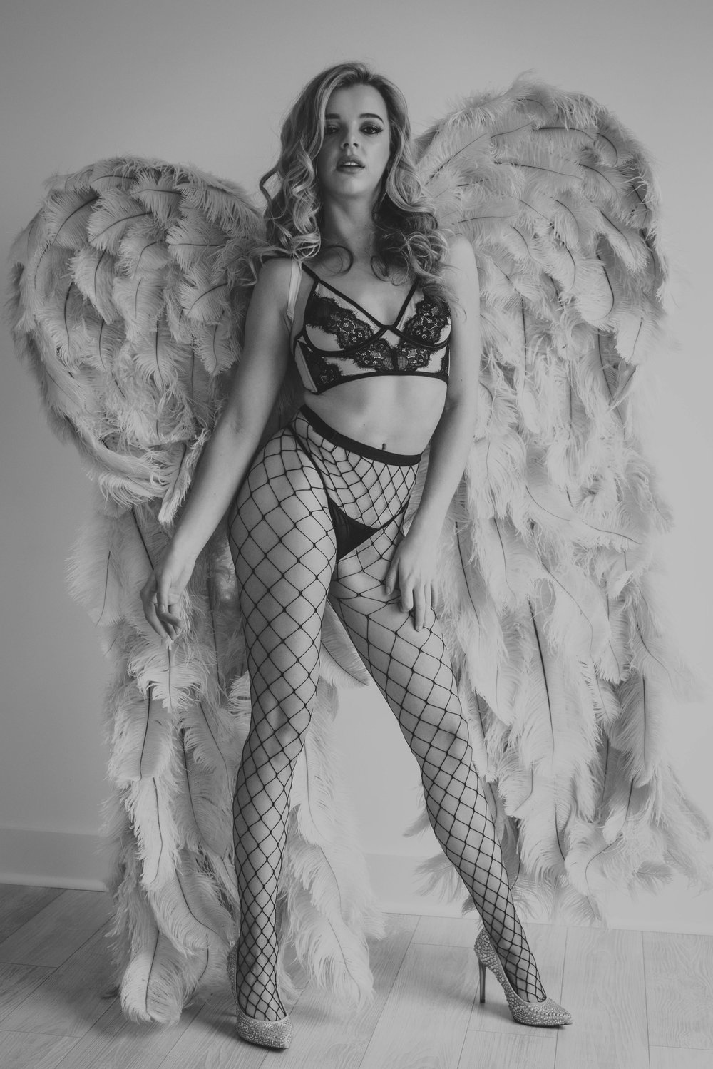 Oklahoma City Boudoir session woman wearing angel wings in power stance