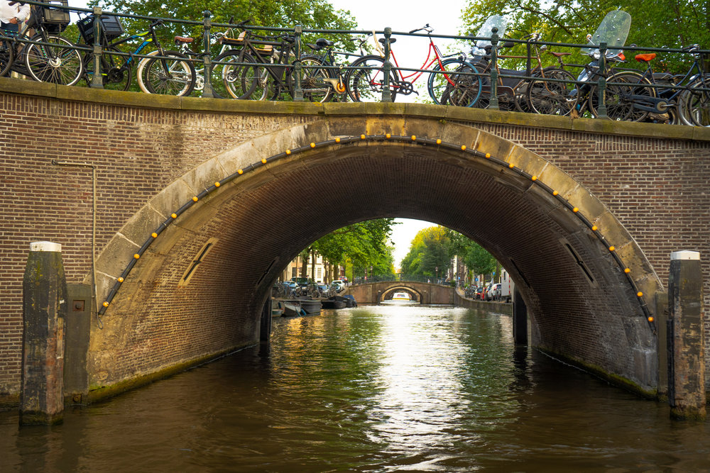Uprooted-Traveler-Amsterdam-canal-bridge-bicycle-vegan-guide-bike.jpg