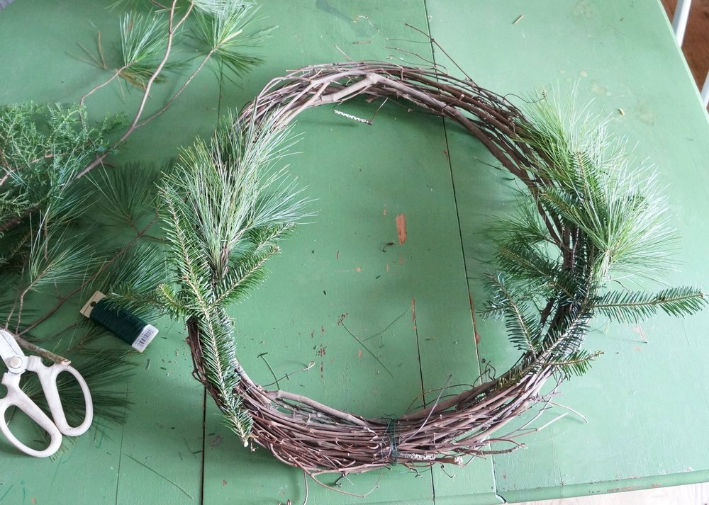 Notice the wire binding the grapevine wreath together…I strategically made that the bottom of my wreath because I knew the wire would be covered by greens.