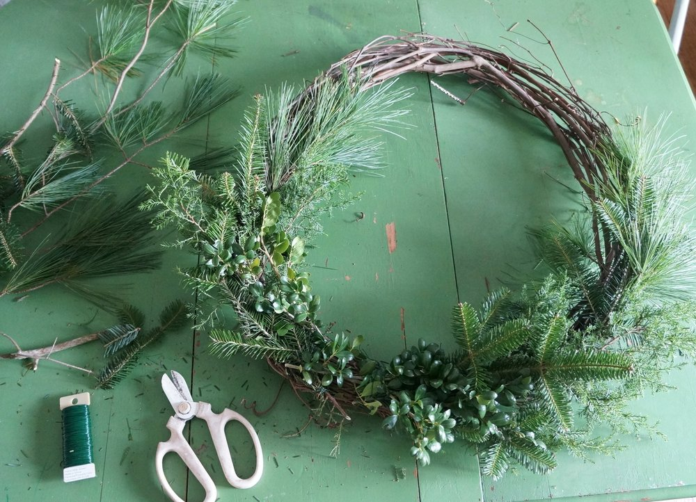 I layered my greens so that the wispy ones were attached first and the stiffer varieties were layered on top. This is mostly personal preference, but it also helps prevent the greens from flopping forward when the wreath is upright.