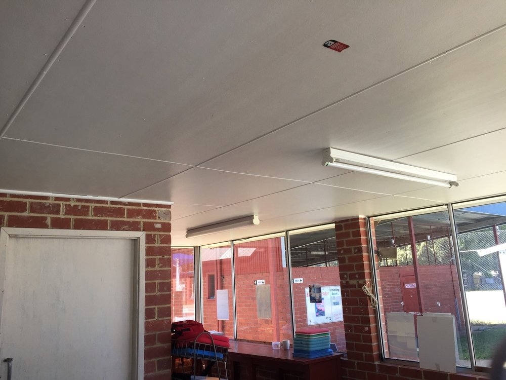 The asbestos register must also note the more common things like this asbestos cement ceiling. The ceiling is in good condition, sealed and labelled. This is the kind of material that can remain as is, provided workers are aware of its location.