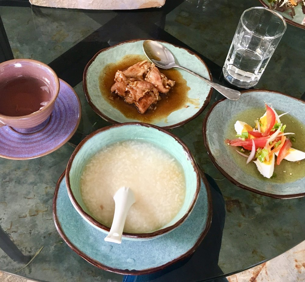 Solid Thai style breakfast of rice soup, pork, and salted egg