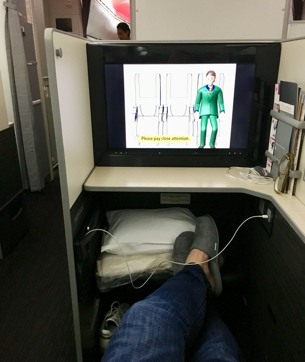 Settling into the JAL Business Class Sky Suite seat 8D with my swanky and comfy JAL-provided slippers