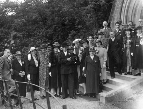 Guests at wedding of Thomas Litster and Jeanie Black, Aberfoyle Church, 12 June 1940. Identified guests are: Meg Black (4th from left in white hat), Lil Black (arm around Meg), Nell Black (in middle with white hat), Julie Litster (to Nell's left in black hat) - Thomas' sister from Galashiels , Mary Black (on church steps, flowery dress), Willy Cooper (to Mary's left) ,Agnes McPhail Litster (nee Bain) (next to Lil wearing fox cape) - Thomas' mother from Galashiels, mrs Beaton (1st from left near fence, next to Meg), Kirsty McAlpine (black hat behind Julie Litster) - daughter of Katherine and Archibald (according to Mr and Mrs Luke of Kinlochard)