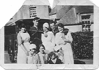 Outside the big house - Grace sitting on one of the servants knees with mother Janet next to her (without a hat) and father Robert at the back with his arms draped around two ladies