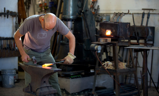 Tom Bennett, a master Blacksmith and Founder of Forgeworks,  forging on his century-old anvil.