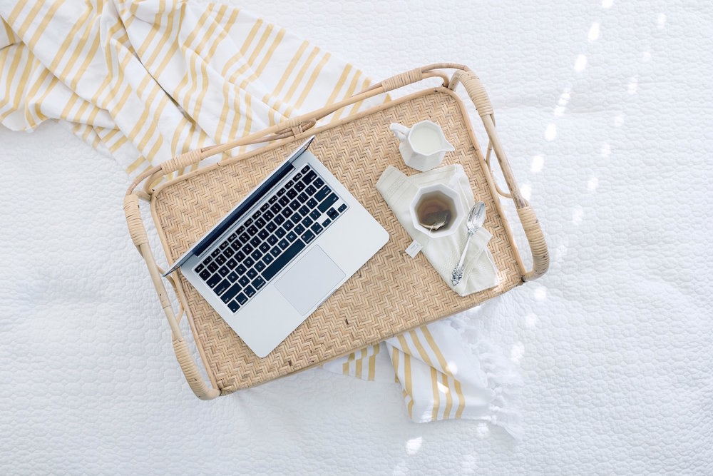 laptop with tea on a tray on a bed.jpg