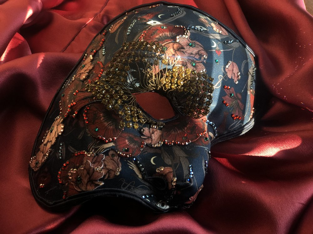 The mask is decorated with a surrealist dark floral satin, 260 Swarovski crystals and a vintage amber crystal flower.