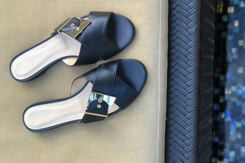 """Gloria - Although I am far past my school days, I typically like to take an adult """"Spring Break"""", which consists of visiting my parents in their retirement community in Florida. I need to pack something that can take me from the beach, to dinner, to drinks (which is an afternoon iced tea, how times have changed!). The Gloria leather sandal is my perfect """"do-all"""" shoe. It's comfortable enough for running around all day, but the gold moon-buckle dresses it up for night (meaning dinner at 5pm, in-bed by 8pm)."""